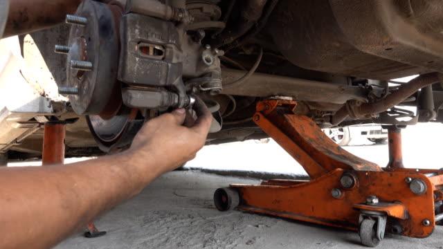 4k: 汽車機械師在汽車車輪制動盤和更換汽車刹車片上的工作 - lebanon 個影片檔及 b 捲影像