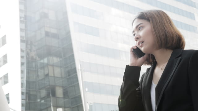 4K:Business woman using smart phone in the central city video