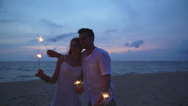 4K:Happy couple lovers lighting sparklers and enjoying freedom at beach during sunset. video