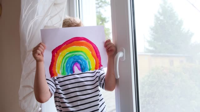 4k.little blonde boy having fun hiding behind a rainbow pattern during covid-19 quarantine at home. let's all be well, hope. chase the rainbow - kids drawing стоковые видео и кадры b-roll