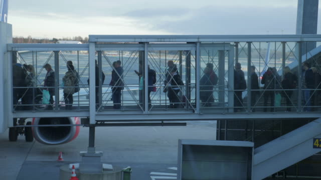 4K:Passengers leave the plane on gangway airplane video