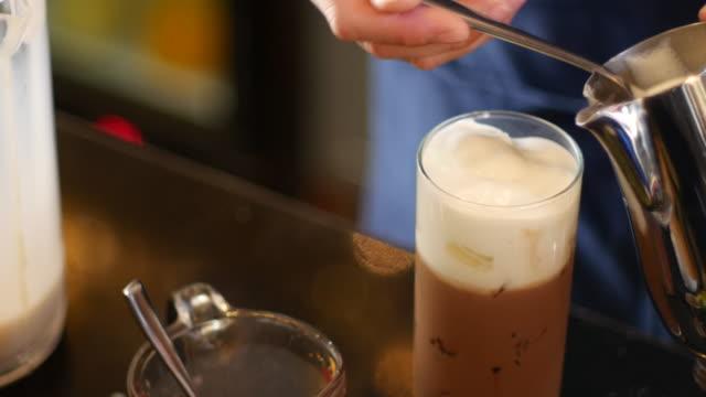 vídeos de stock e filmes b-roll de 4 k: verter o leite no café latte e caneca de café - café gelado