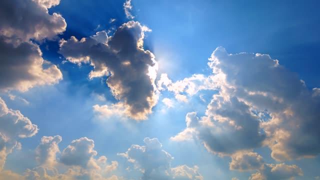 4 k。時間経過動く雲と白い雲と太陽光線の青い空に飛んで - 多重露出点の映像素材/bロール