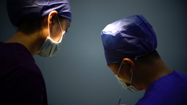 4K:Two Asian surgeons with face mask in the operating room,Shanghai,China video