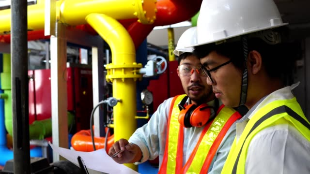 4K:Two male Asian engineers are checking the gas system of the factory