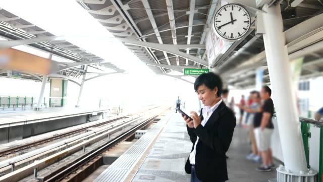 4k:Women waiting the train and Using smart phone. video