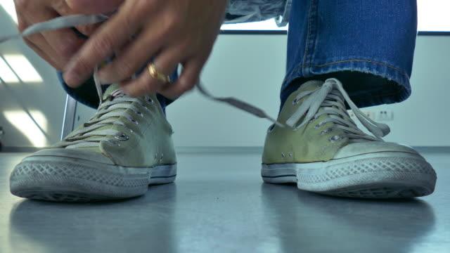 4 k: young 男性結束靴 - 結ぶ点の映像素材/bロール