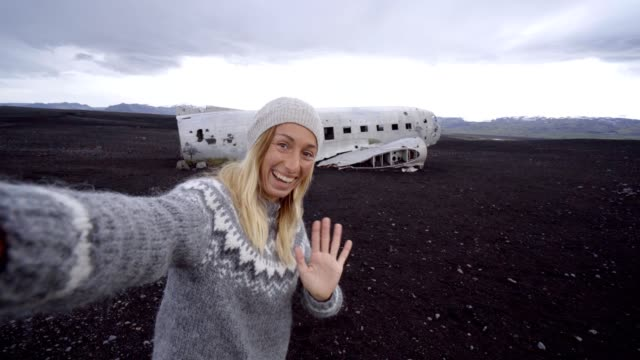 4K-Young woman standing by airplane wreck on black sand beach taking a selfie portrait Famous place to visit in Iceland and pose with the wreck video