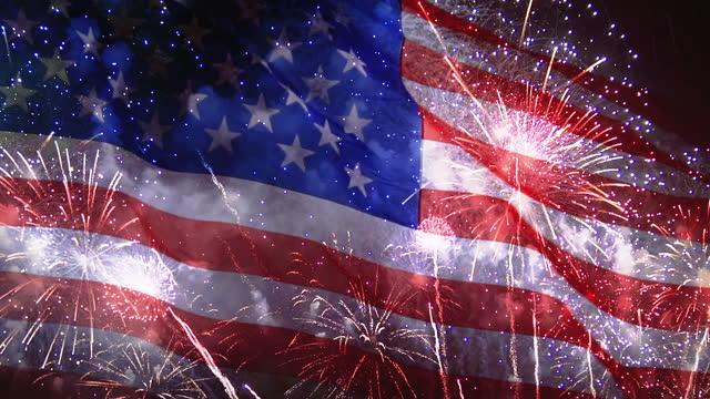 vídeos y material grabado en eventos de stock de 4 de julio de fondo con fuegos artificiales sobre ondear la bandera de estados unidos, celebración día de la independencia en américa - independence day