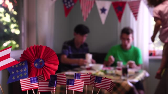 4th of July. Independence Day in the United States. Family Patriotic party. American flag decor at home The Fourth of July Celebrations in the USA. Festive food and holiday. The happy American family is celebrating, talking and eating together family 4th of july stock videos & royalty-free footage