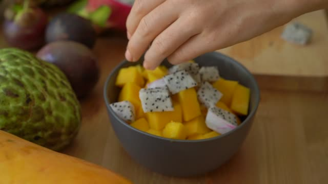 4x times slowmotion shot of a young woman putting the dragon fruit cubes into a grey ceramic bowl and lots of tropical fruits lay on a table - pitaja filmów i materiałów b-roll
