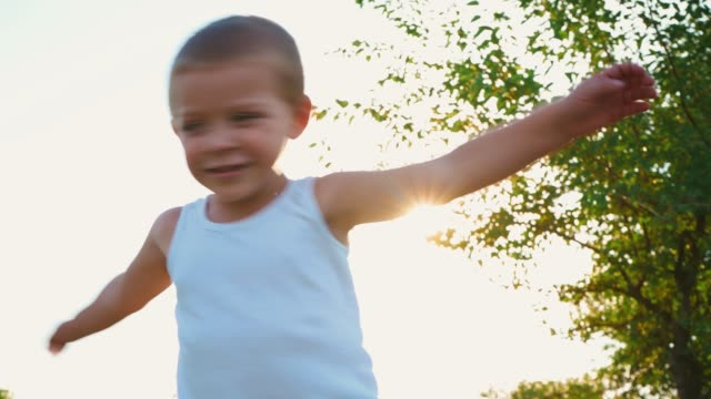 4-year-old boy in a white t-shirt laughs and stretches out his hands. Portrait of a cheerful active child on a nature background 4-year-old boy in a white t-shirt laughs and stretches out his hands. Portrait of a cheerful active child on a nature background. Happy childhood. only boys stock videos & royalty-free footage