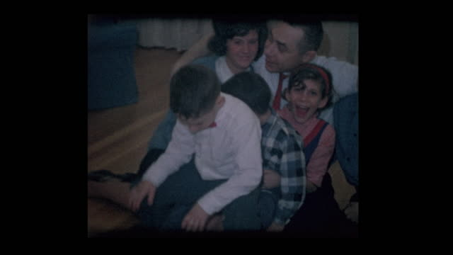 60s family getting ready for photo in mans lap