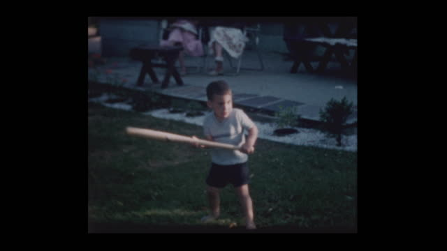 60s Family plays with little boy with bat and big yellow ball video