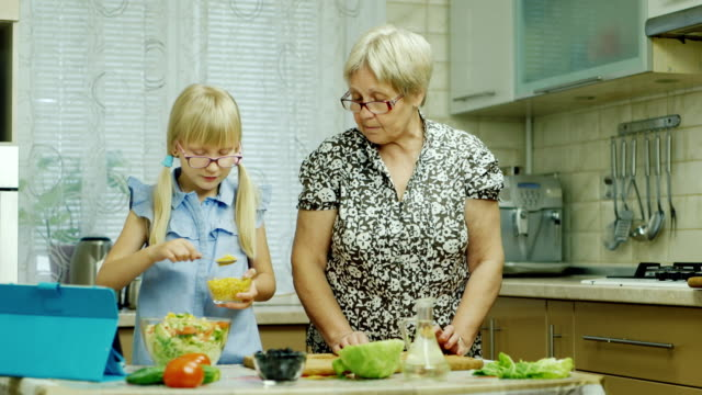 A 6-year-old girl in pink glasses prepares a salad in the kitchen. Her grandmother helps, use a tablet video