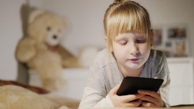 en 6-årig flicka läser en e-bok i sitt sovrum - digital reading child bildbanksvideor och videomaterial från bakom kulisserna