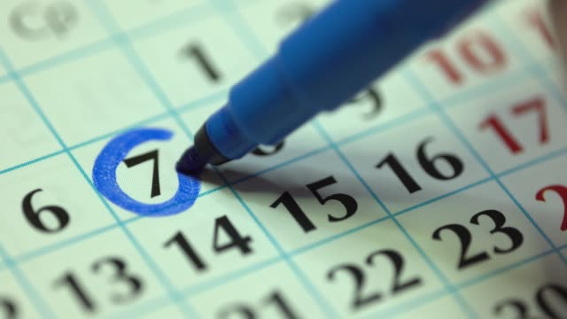 7th – seventh day of the month. The woman marks the calendar date with a blue marker