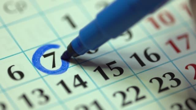 7 - siódmy dzień miesiąca. kobieta oznacza datę kalendarza niebieskim markerem - data filmów i materiałów b-roll