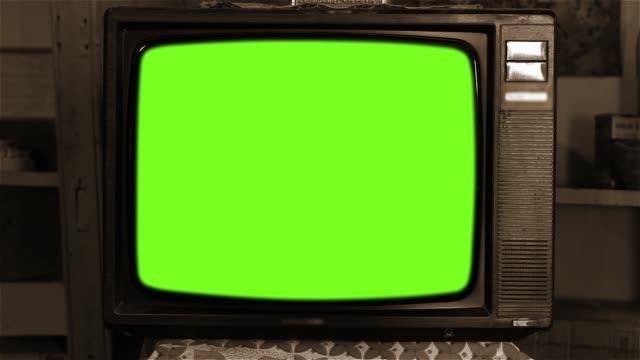 80er jahre fernsehen mit grünem bildschirm. sepia ton. - tv stock-videos und b-roll-filmmaterial