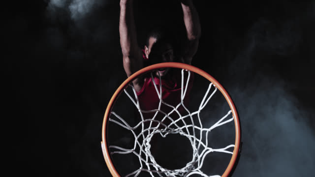 stockvideo's en b-roll-footage met slo mo of a basketball player in red performing slam dunk shot - basketbal teamsport