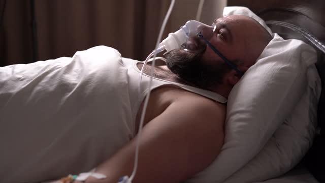 a bearded Caucasian man lies sick, lies in a hospital, breathing through an oxygen mask. artificial lung ventilation