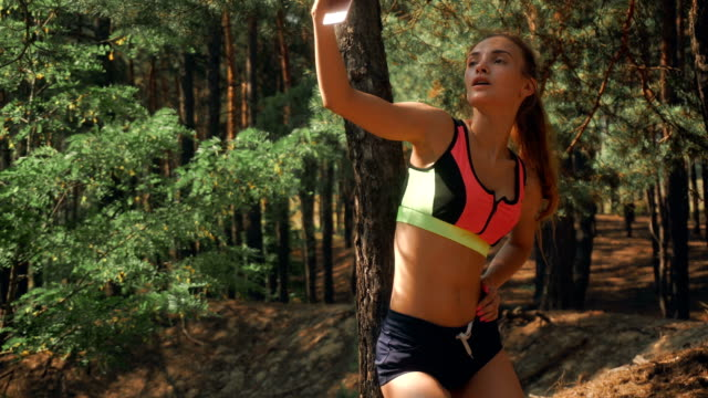 a beautiful athlete makes photo on the phone in the forest video