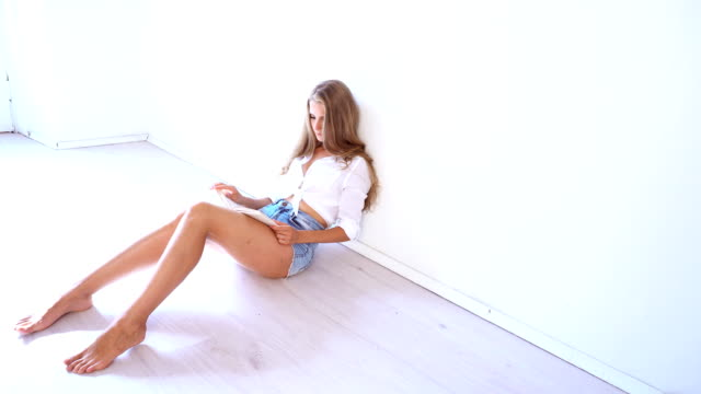 a beautiful girl sitting in a white room and reads a book video
