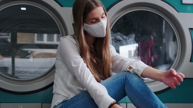 a bored young lady student wearing a protective face mask sitting on the floor nearby an industrial washing machine