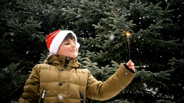 a boy in a red cap of Santa Claus looking at a sparkler fire video