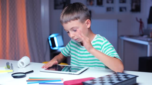 a boy sits at a table, uses a tablet while doing school