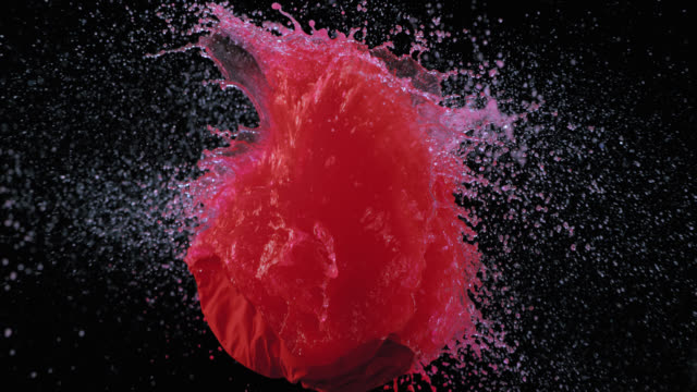 SLO MO of a bullet piercing a red water balloon video