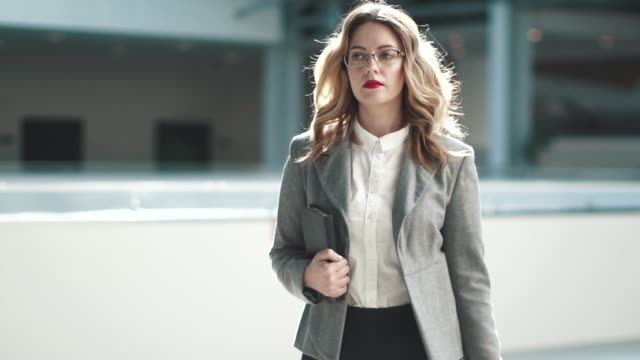 a business woman in a gray jacket goes to the lobby of the business center. girl in a business suit in the workplace. slow motion - autorità video stock e b–roll