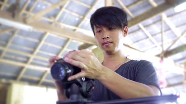a Camera man with a mirrorless camera moving dolly slider at indoor locations.