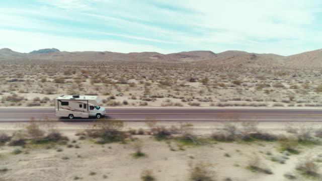 stockvideo's en b-roll-footage met een camper die door de woestijn mojave op een de zomerdag drijft - caravan