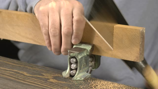 a carpenter saws a blank for a wooden comb with a Japanese saw video