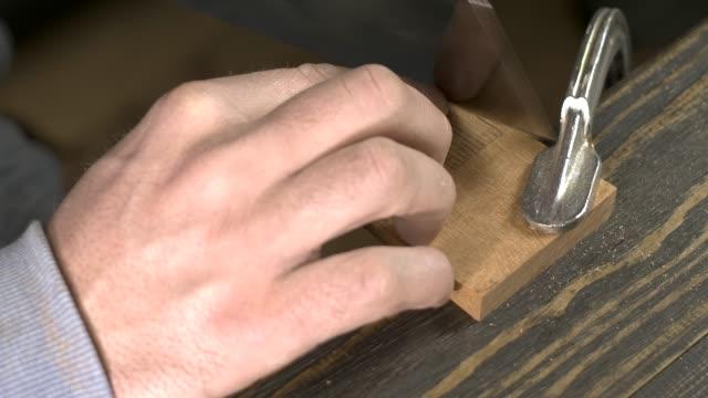 um carpinteiro serra um em branco para um pente de madeira com uma serra japonesa - vídeo