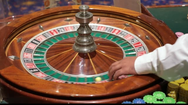 a casino dealer spins roulette hand