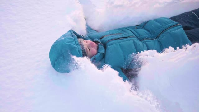 vídeos de stock e filmes b-roll de a child fall in the snow in slowmotion. snow storm. sports outdoors. active lifestyle. - roupa quente