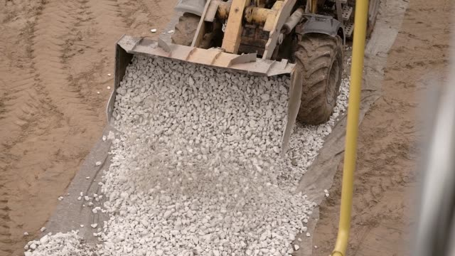 a close shot on a metal ladle, heavy machinery unloads small stones, pebbles on the road, in order then to put there asphalt - ghiaia video stock e b–roll