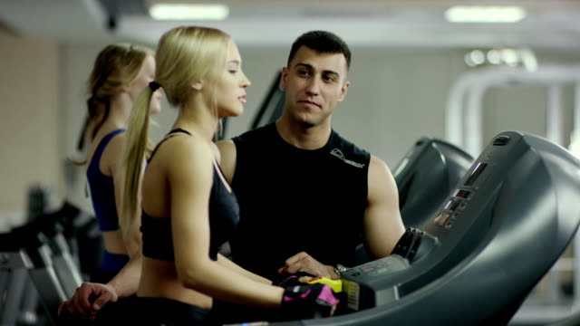 a coach give the high five to the woman walking on the treadmill - cleavage stock videos & royalty-free footage