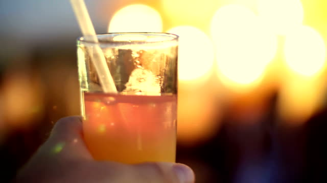 a cocktail party, a beverage with ice in a glass with a tube, in the rays of soffits, lamps, flickering lights. original alcoholic and non-alcoholic cocktails - rum superalcolico video stock e b–roll