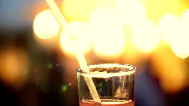 a cocktail party, a beverage with ice in a glass with a tube, in the rays of soffits, lamps, flickering lights. original alcoholic and non-alcoholic cocktails video