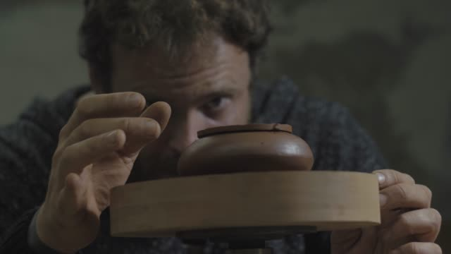 a craftsman rotates a teapot made of clay yixing on a wooden shaft. Handmade clay teapot Yixing for tea ceremony.brown pottery teapot. 4k video. 59.94 fps