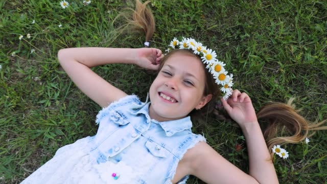 a cute little girl lying on green grass. camomiles. daisies. the child strongly laughs