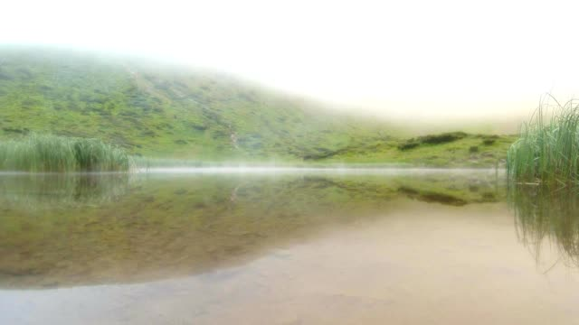 a Dense Fog is Lowered on a Small Lake in The Mountains video