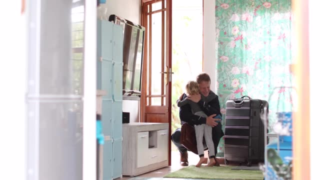 a Father arrives home after a business trip. a Father arrives home after a business trip. homecoming stock videos & royalty-free footage