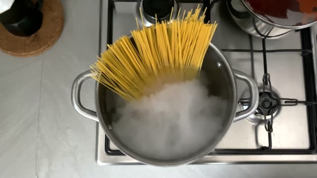 a female hand puts raw spaghetti in the boiling water contained in a pot to cook them. Italian cuisine a female hand puts raw spaghetti in the boiling water contained in a saucepan to cook them. Italian cuisine. Raw food. interior of a domestic kitchen. Food preparation and cooking condensation stock videos & royalty-free footage