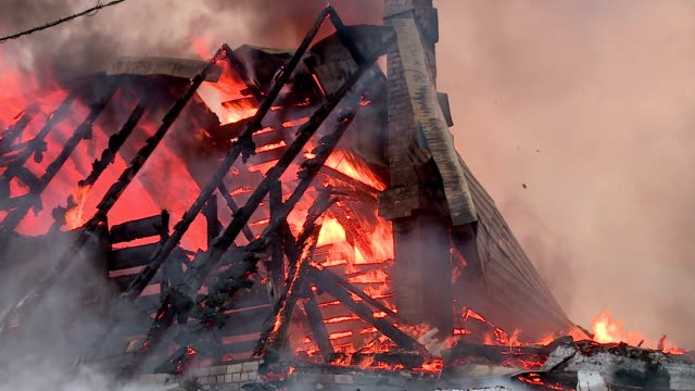 a fire in the village lit cottage in the winter - incendio doloso video stock e b–roll