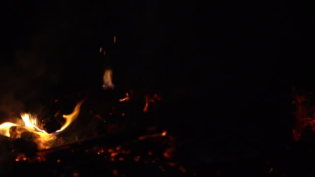 a fire is burning at night sparks fly video