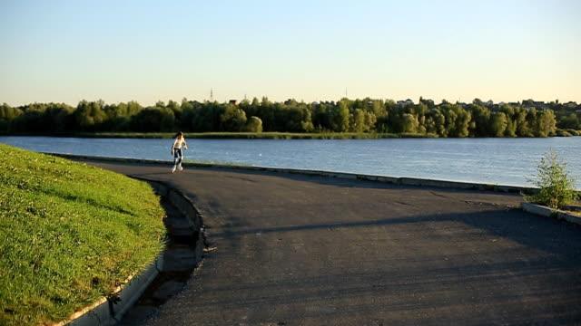 stockvideo's en b-roll-footage met een meisje in een wit t-shirt met mooie staarten in jeans is schaatsen in de buurt van de rivier op een zomeravond bij zonsondergang. sport, actieve levensstijl, gelukkige jeugd. - wit t shirt